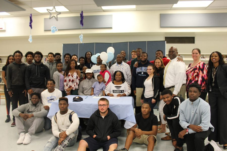 Palmetto's football family and administration join senior Kenneth Spiller at the table where he chose to play football for Charleston Southern University.​