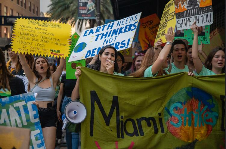 Miami protestors hold up their signs proudly as they stand up for climate change action.