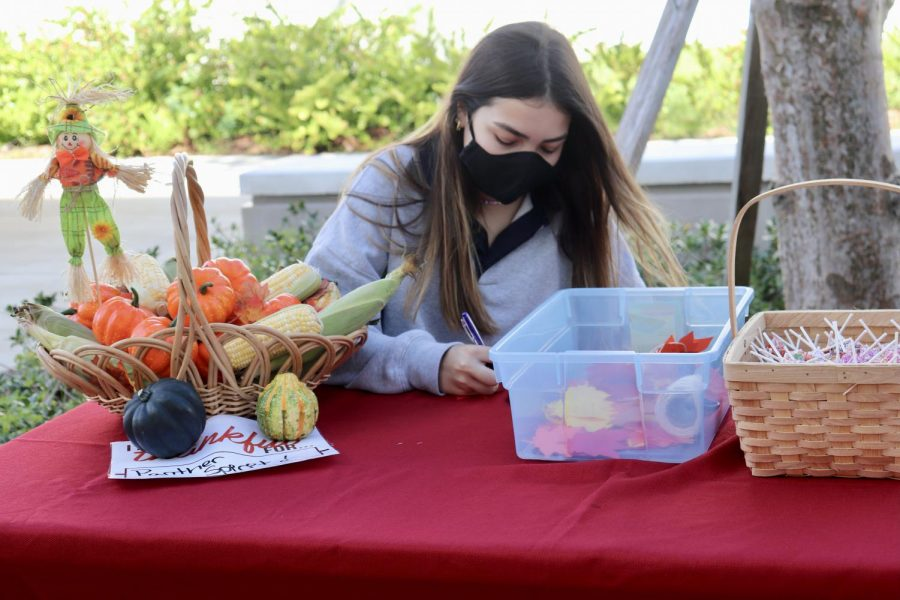 Senior Olivia Glatzer sets up the fall leaves before students arrive. During lunch, the students could write a statement on a leaf, pledging to give back to their community this Thanksgiving season. In return, students received a lollipop of their choice.