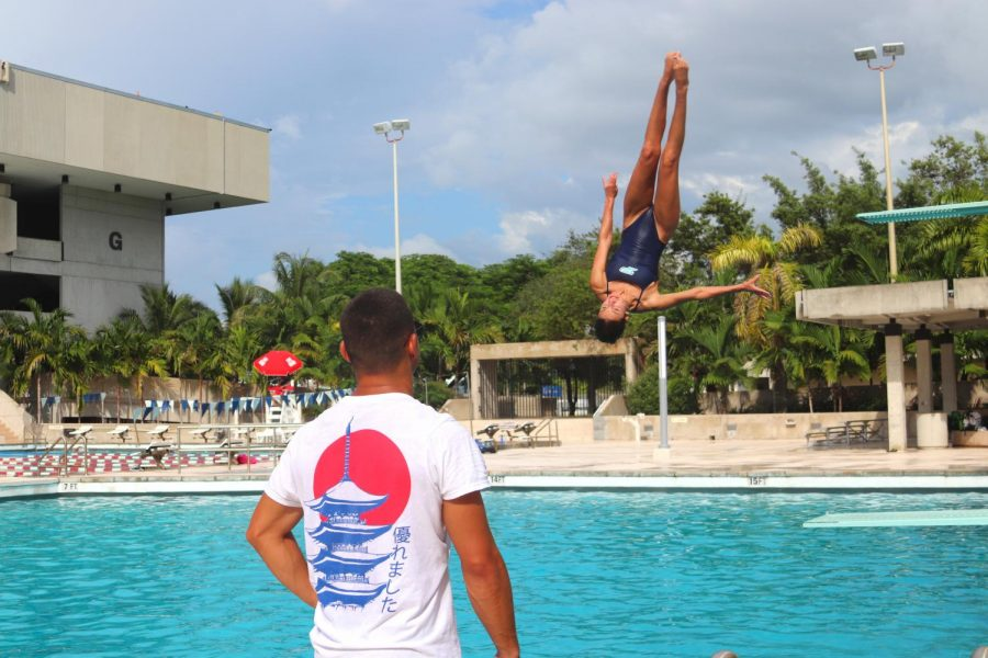 Coach Briadam Herrera critiques Senior and Dive Team Captain Isabella Reyess dive during practice.